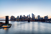 New York City, Lower Manhattan Skyline with Brooklyn Bridge and East River at twilight, elevated view.