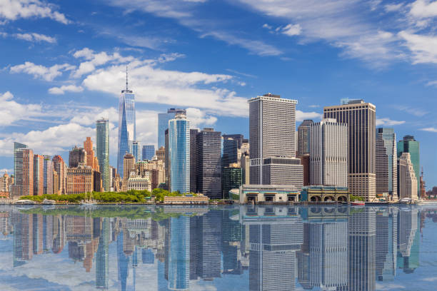 new york city skyline with manhattan financial district and world trade center reflected in water of new york harbor, ny, usa. - lower east side manhattan stock pictures, royalty-free photos & images