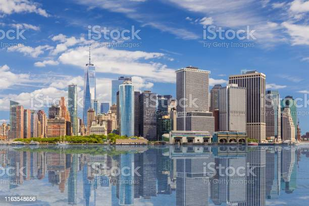 Photo of New York City Skyline with Manhattan Financial District and World Trade Center Reflected in Water of New York Harbor, NY, USA.