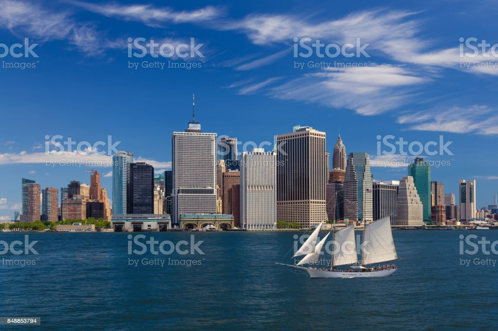 New York City Skyline with Manhattan Financial District, Battery Park, Sailboat (Tall Ship), Water of New York Harbor and Blue Sky. stock photo
