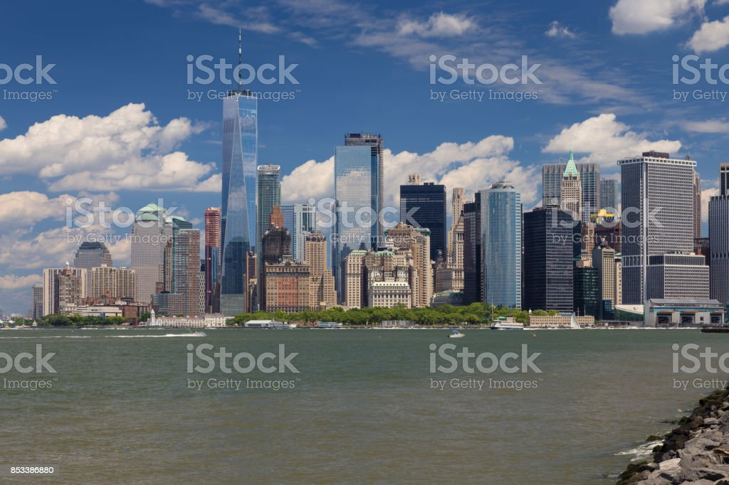 New York City Skyline with Manhattan Financial District, Battery Park, Staten Island Ferry Terminal, Water of New York Harbor, World Trade Center and Blue Sky. stock photo