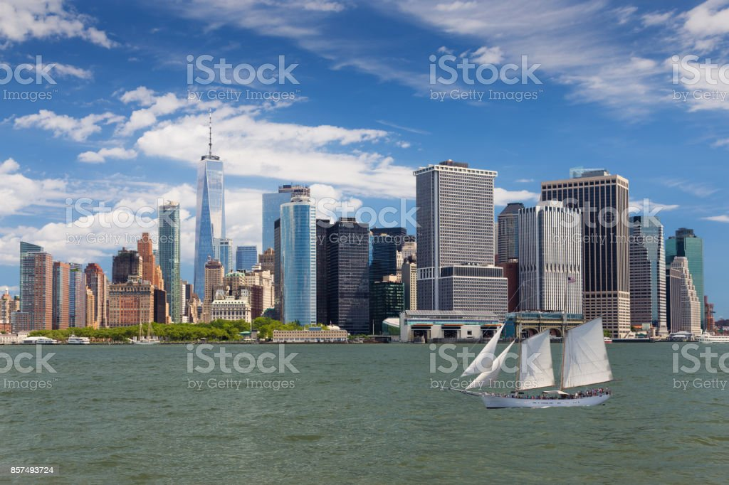 New York City Skyline with Manhattan Financial District,  Battery Park, Sailboat (Tall Ship), Water of New York Harbor, World Trade Center, Staten Island Ferry Terminal and Blue Sky. stock photo