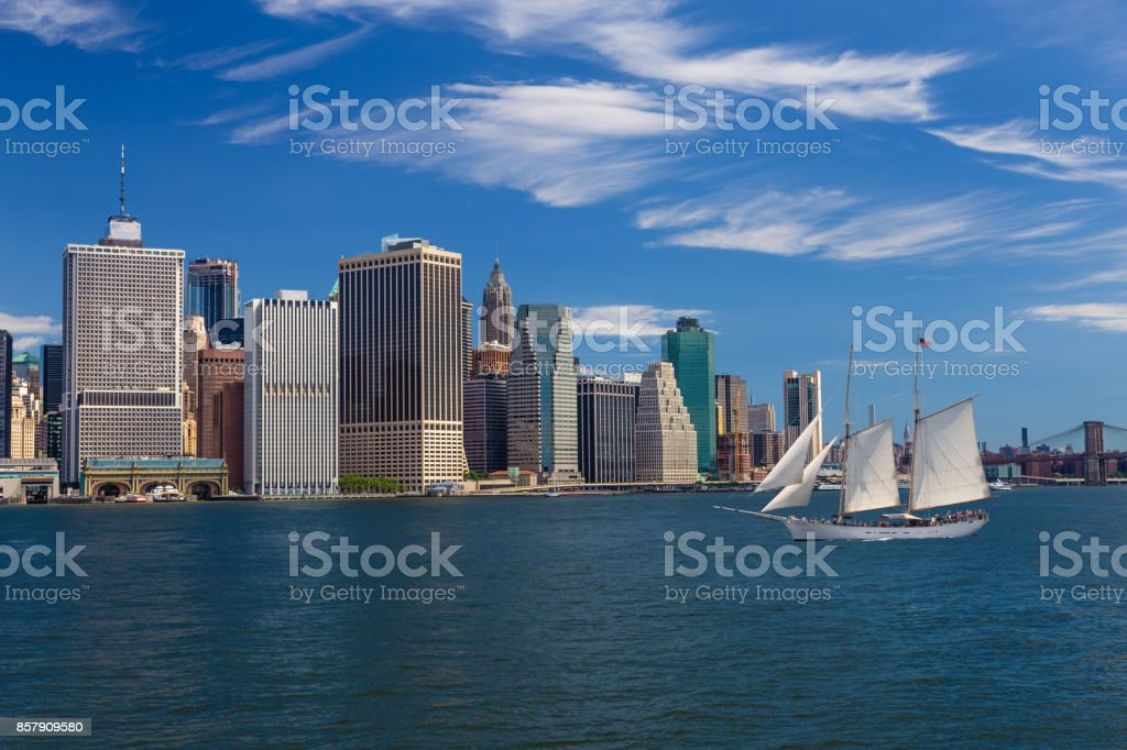 New York City Skyline with Manhattan Financial District, Brooklyn Bridge, Sailboat (Tall Ship), Water of New York Harbor and Blue Sky. stock photo
