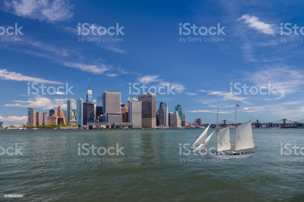 New York City Skyline with Manhattan Financial District, Sailboat (Tall Ship), Water of New York Harbor, Battery Park, Brooklyn Bridge and Blue Sky. stock photo