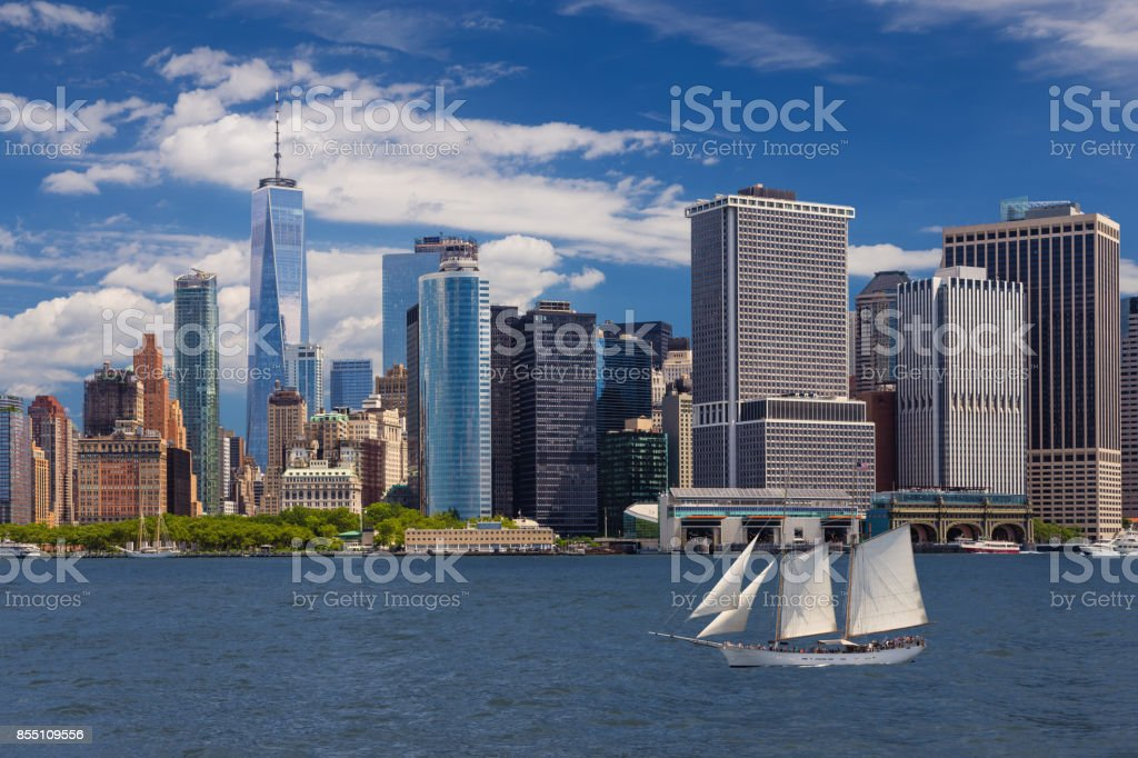 New York City Skyline with Manhattan Financial District, Sailboat (Tall Ship), Water of New York Harbor, World Trade Center, Staten Island Ferry Terminal and Blue Sky. stock photo