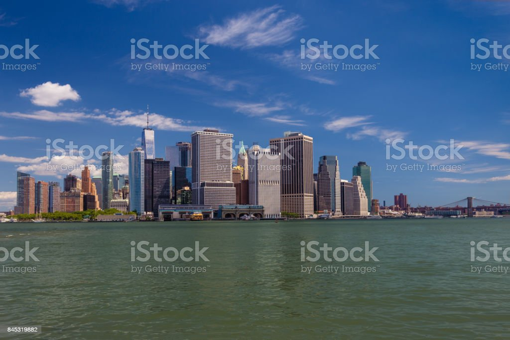 New York City Skyline with Manhattan Financial District, Water of New York Harbor, World Trade Center, Brooklyn Bridge and Blue Sky. stock photo
