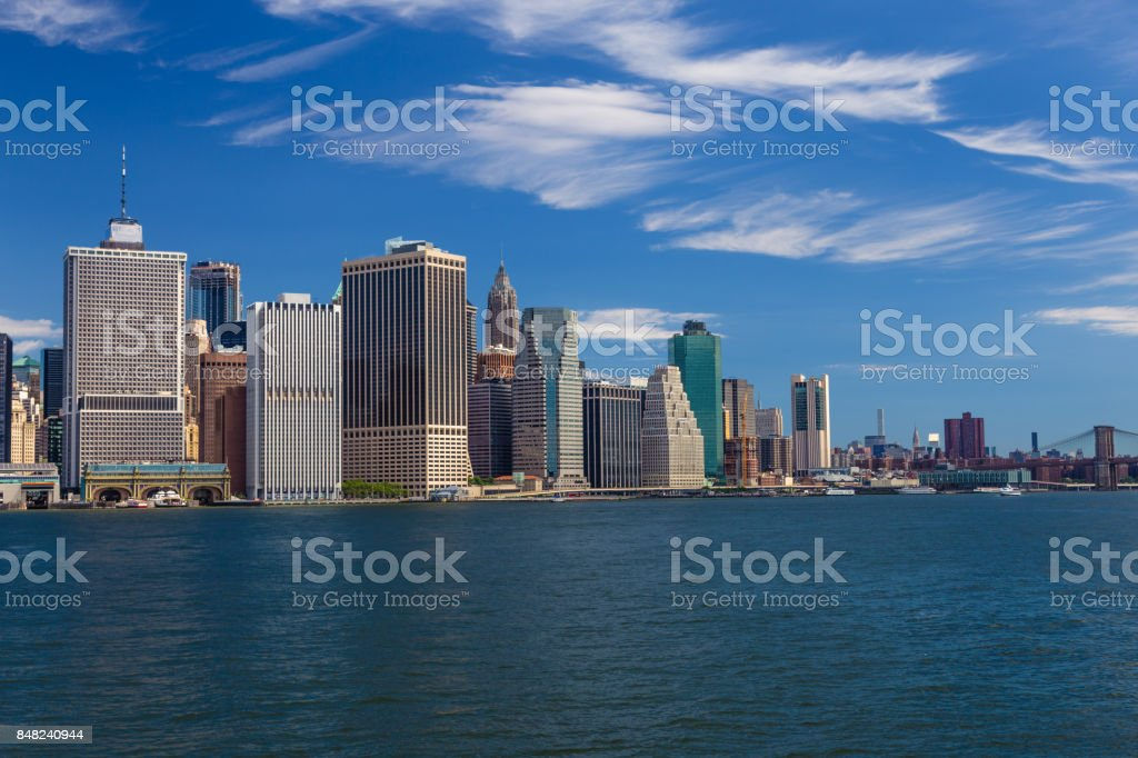 New York City Skyline with Manhattan Financial District, Water of New York Harbor, FDR Drive, Brooklyn Bridge and Blue Sky. stock photo