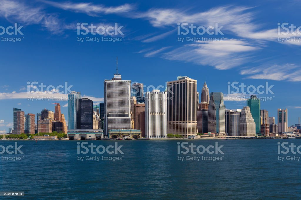 New York City Skyline with Manhattan Financial District, Water of New York Harbor, Battery Park, FDR Drive and Blue Sky. stock photo