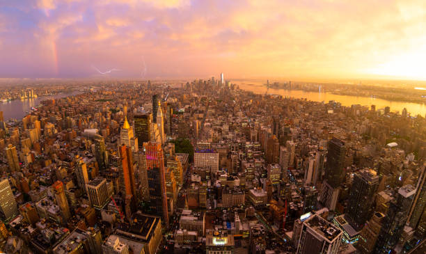 New York City skyline with Manhattan skyscrapers at dramatic stormy sunset, USA. New York City skyline with Manhattan skyscrapers at dramatic vibrant after the storm sunset, USA. Rainbow and lightnings can be seen in background over Brooklyn bridge. new york city stock pictures, royalty-free photos & images