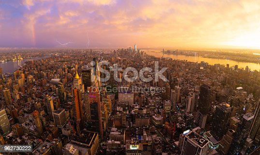 New York City skyline with Manhattan skyscrapers at dramatic vibrant after the storm sunset, USA. Rainbow and lightnings can be seen in background over Brooklyn bridge.