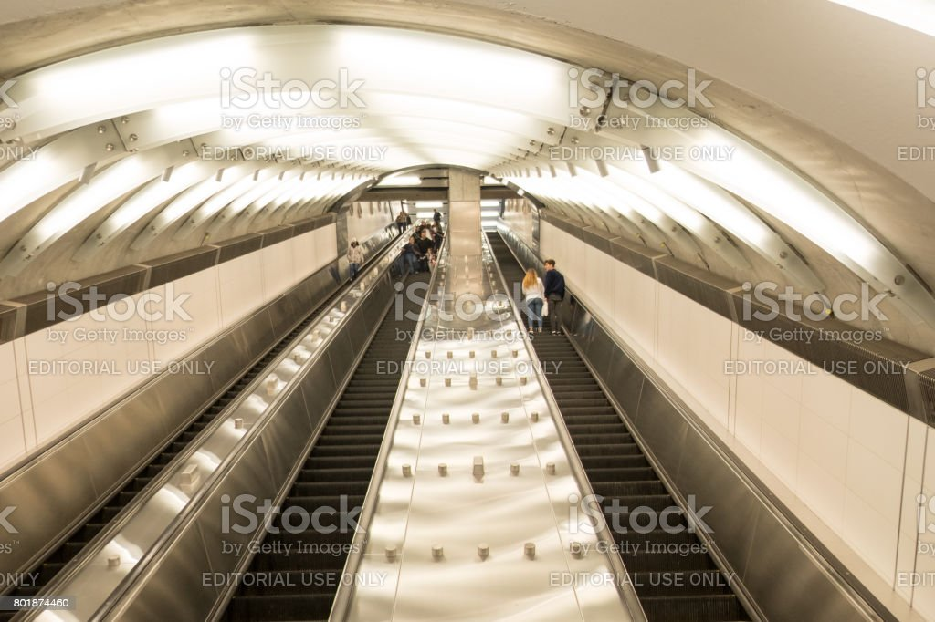 New York City subway escalators going down the long tunnel to the 86th Street station, Upper East Side. People riding the escalator down to the subway entrance. stock photo