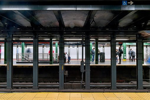 Timesquare Newyork,United States:Nov 29 2019 :crowd people waiting and boarding trains at subway\n station platform in New York city, USA. American city life public commuter transportation