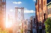 New York City street scene with sunlight shining on the Williamsburg Bridge in Brooklyn NYC