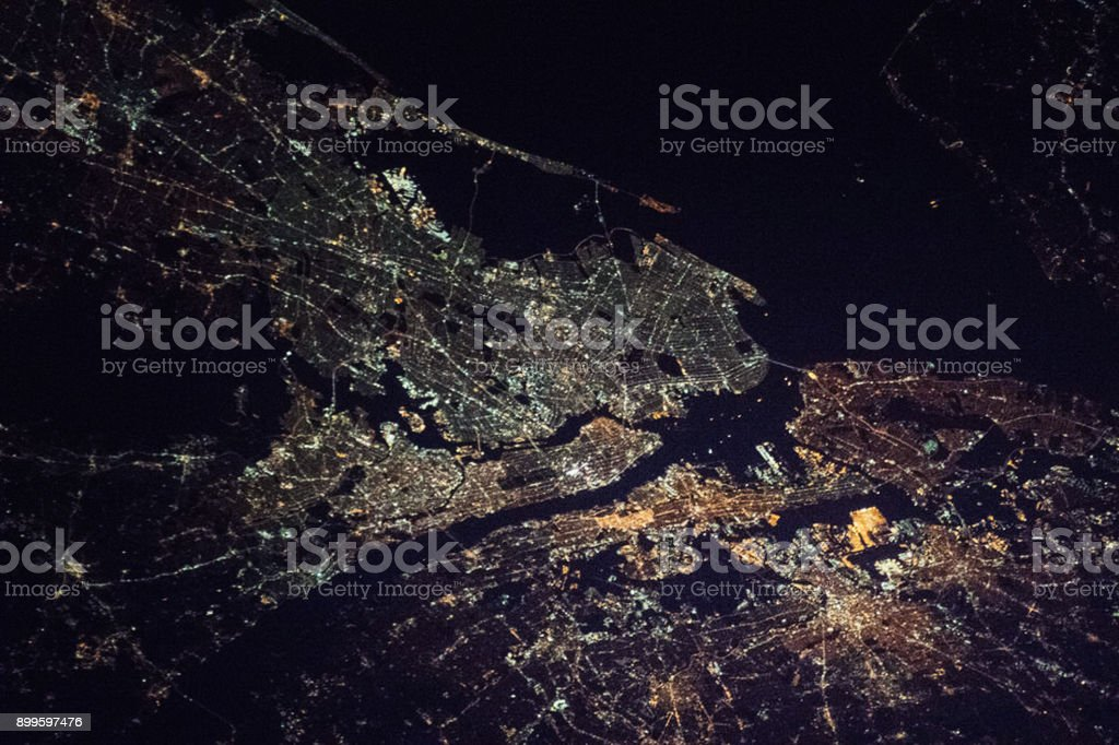 New York City - the Bronx, Manhattan, Queens, Brooklyn and Staten Island, and part of the state of New Jersey night space view (elements of image furnished by NASA) stock photo