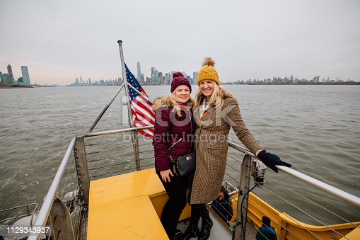 Two women commuting via a tour boat to go across to the Statue of Liberty in New York City.