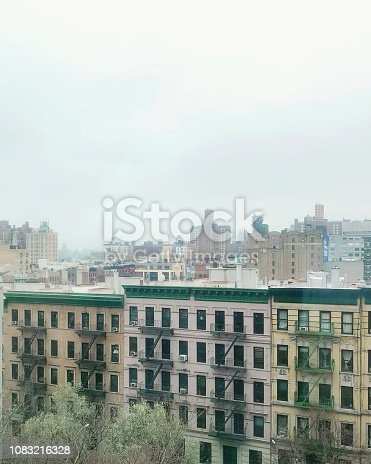 Looking out at multicolored New York City Upper West Side apartments with a city view in the background. Rooftop view.