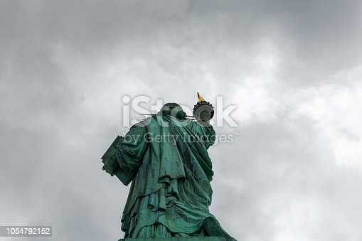 The statue of liberty back view in cloudy sky in New York City United States