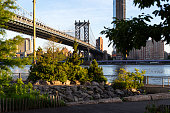 New York City / USA - JUN 25 2018: Brooklyn Bridge Park with Lower Manhattan skyline at sunrise