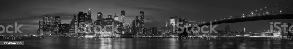 New York city with Brooklyn Bridge, iconic skyline panorama at night in black and white stock photo