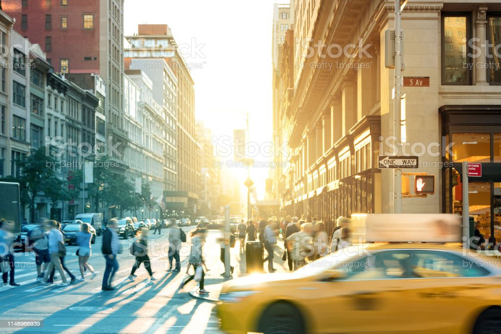 New York City yellow taxi cab speeds past the crowds of people at the...
