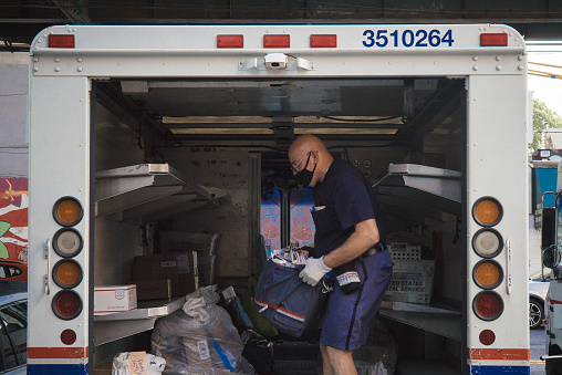 Queens, New York. June 24, 2020. A mail man waring a face mask inside a truck getting ready to deliver.