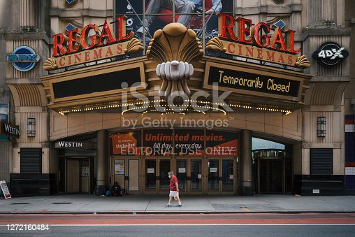 Manhattan, New York. August 26, 2020. A man wearing a mask walks in front of a temporarily closed movie theatre on 42nd street in Midtown.