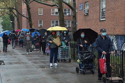 Queens, New York. October 28, 2020. A large crowd of people wait in line outside an outdoor food pantry in Woodside organized by