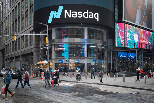 Manhattan, New York. December 23, 2020. People walking in front of Nasdaq market site  located at 4 Times Square.
