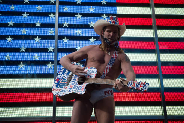 New York during the COVID-19 emergency. Manhattan, New York. January 20, 2021. Naked Cowboy performs in front of US flag during the presidential inauguration. joe biden stock pictures, royalty-free photos & images