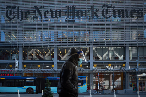 Manhattan, New York. January 28, 2021. A man wearing a mask and a face shield walks in front of the New York Times building in Midtown.