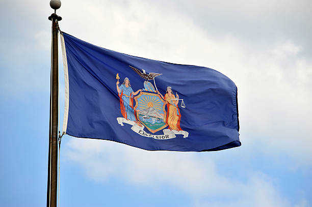 New York Flag New York Flag flying in the wind with beautiful sky on the background. albany county new york state stock pictures, royalty-free photos & images
