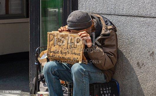 istock New York, Manhattan downtown. Homeless man holding a cardboard sign, begging 1157133562