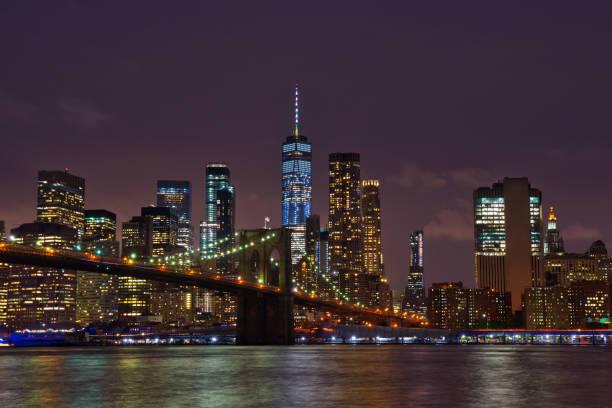 New York Manhattan skyline and Brooklyn Bridge by night