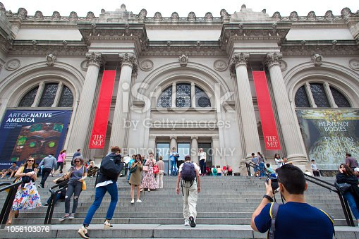 New York, NY: A diverse crowd on the steps of the Metropolitan Museum of Art on Manhattan's Upper East Side, walking up and down and taking photos.
