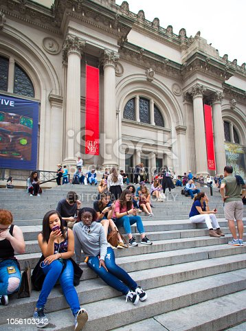 New York, NY: A diverse crowd relaxes on the steps of the Metropolitan Museum of Art on Manhattan's Upper East Side, most looking at their smart phones.