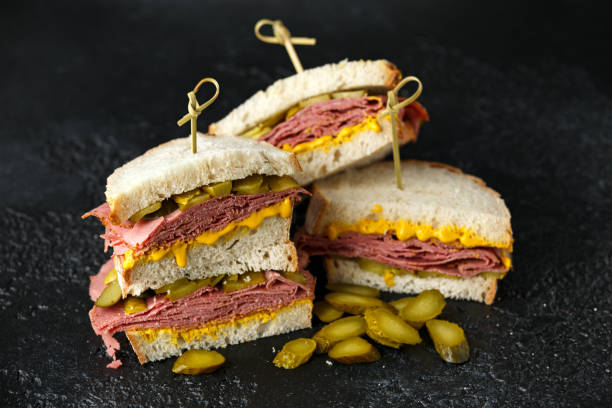 new york pastrami, gherkins and sourdough bread deli sandwich - pastrami stock pictures, royalty-free photos & images