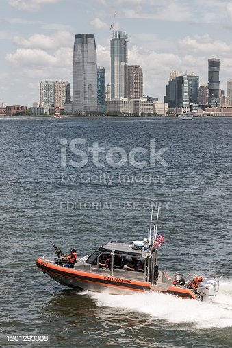 New York, USA - Jul 24, 2019: The Coast Guard patrolling the New York harbor off Lower Manhattan and escorting the Staten Island Ferry late in the day.