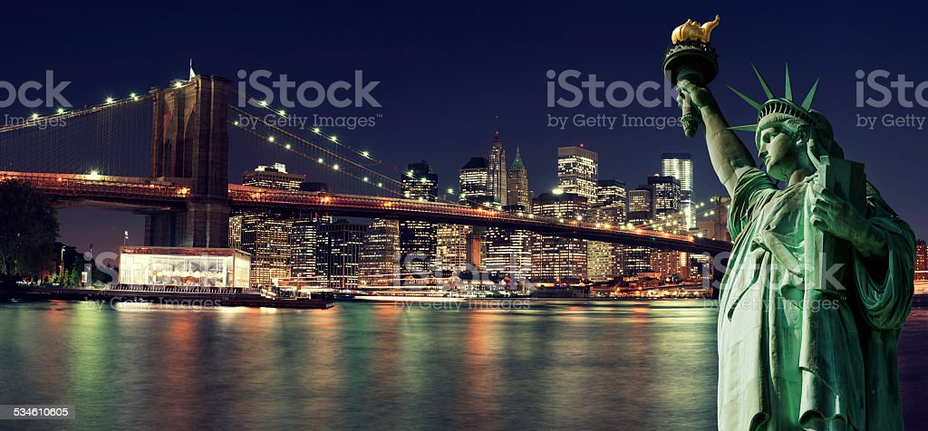 New York Skyline at night with Statue of Liberty stock photo