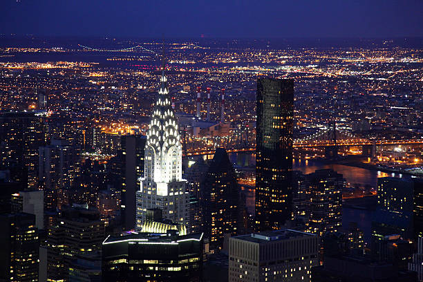 new york skyline illuminated at night - chrysler building stock photos and pictures