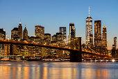 Brooklyn Bridge, East River, and Lower Manhattan, New York City skyline illuminated at dusk, HDR image.