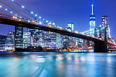 New York skyline with Brooklyn Bridge illuminated at night. In the background is seen Manhattan skyline with the One World Trade Center - Freedom Tower and Beekman Tower on the right side, the tallest residential tower in world, designed by Frank Gehry. horizontal orientation, America, USA.