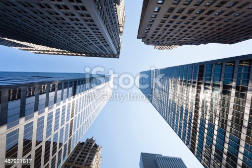 Straight up view of skyscrapers in Manhattan in New York with blue sky.