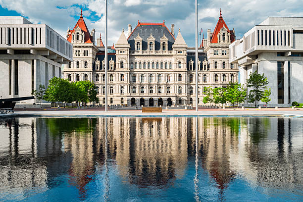 New York State Capitol in Albany New York USA Photo of the New York State Capitol with reflections in a pond. It is the seat of the New York State government, located in downtown Albany, New York, USA. albany county new york state stock pictures, royalty-free photos & images