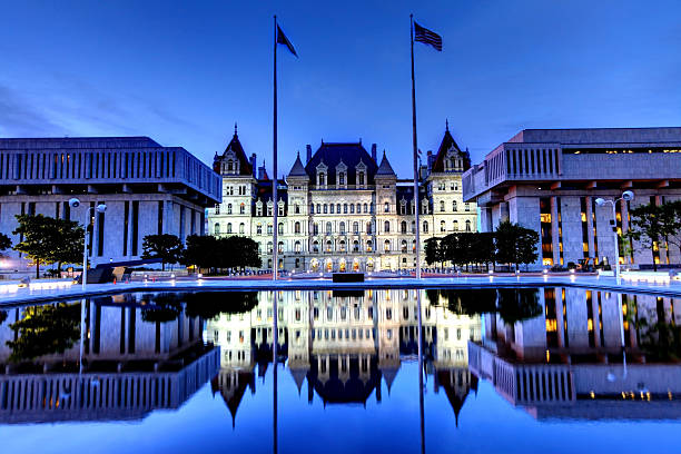 New York State Capitol New York State Capitol is the state capitol building of the U.S. state of New York located in Albany. The capitol is reflecting in a pool in  Rockefeller Empire State Plaza. Albany is known for its culture, history, architecture, and institutions of higher education albany county new york state stock pictures, royalty-free photos & images