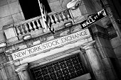 """""""New York City, USA - May 04, 2010: New York City Stock Exchange entrance with Wall Street sign and American flag. Capital Letters on Marble. Blue monochrome photo."""""""