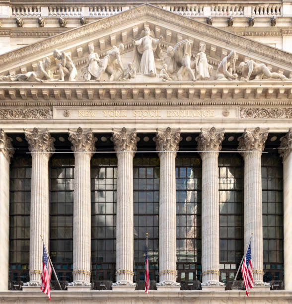 New York Stock Exchange exterior view in the financial district of Manhattan NEW YORK CITY - CIRCA 2019: American flags hang above the entrance of the historic New York Stock Exchange building in the financial district of Manhattan. manhattan financial district stock pictures, royalty-free photos & images