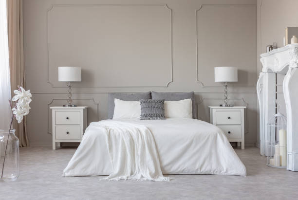 New york style bedroom interior with symmetric design, copy space on empty grey wall