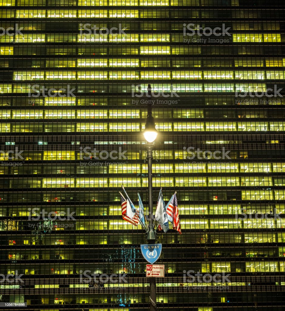New York, UN Way sign with flag, United Nation building unsharp in...