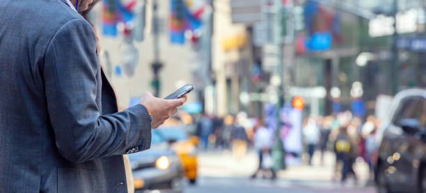 new york, wall street. young man in suit holding a smartphone - city walking background foto e immagini stock