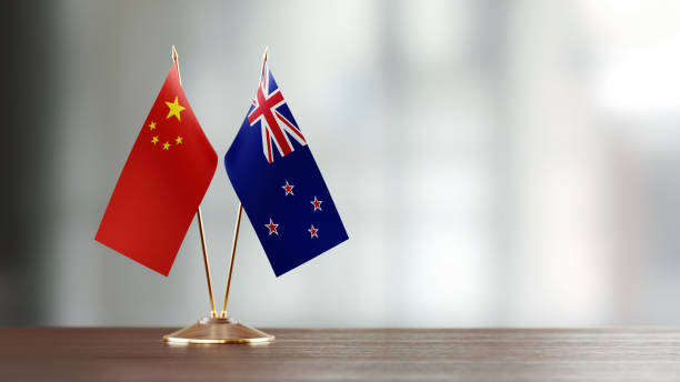 new zealand and chinese flag pair on a desk over defocused background - new zealand flag stock photos and pictures